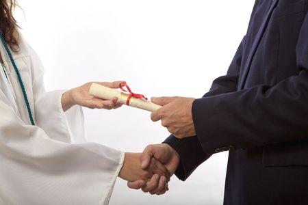 graduate receiving her diploma and a handshake
