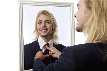 adjusted: young man in a mirror getting his tie adjusted by his reflection