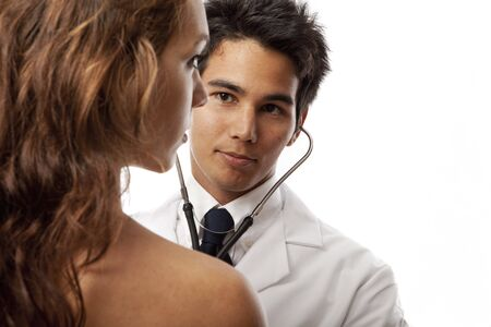 young asian doctor listening to the heartbeat of a female patient with his stethoscope Фото со стока