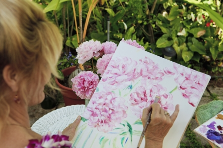 female artist in her fifties painting flowers outdoors