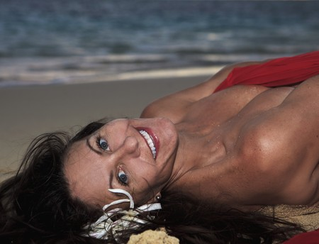 forty year old woman in red chiffon on the beach in hawaii photo