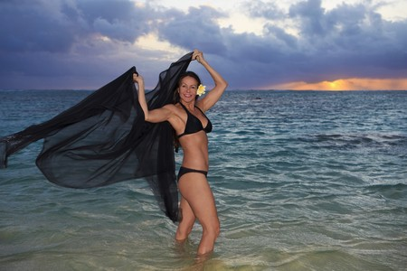 beautiful forty year old woman in the ocean at sunrise in hawaii Stock Photo