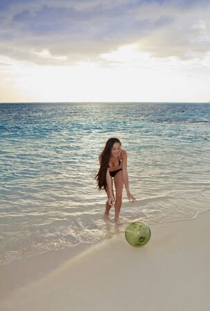 young woman discovers a glass float net ball on a hawaii beach