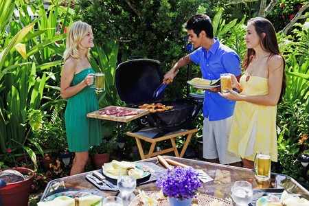 drie vrienden met een barbecue lunch in de tropische tuin  Stockfoto