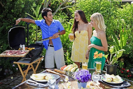 three friends having a barbecue lunch in their tropical garden photo