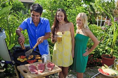 trzech przyjaciół posiadajÄ…ce obiad grill w ich Ogród tropikalny Zdjęcie Seryjne