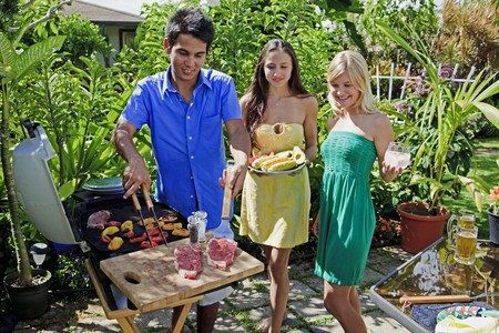 backyard woman: three friends having a barbecue lunch in their tropical garden Stock Photo