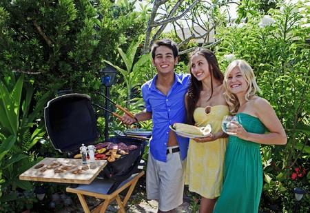 熱帯庭でバーベキューの昼食を持っている 3 人の友人