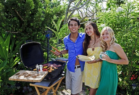 three friends having a barbecue lunch in their tropical garden Archivio Fotografico