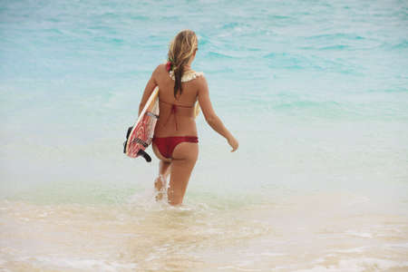 teenage girl in the ocean with her surfboard at kailua beach photo