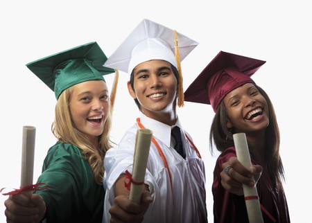 cap and gown: three graduates in cap and gown with diplomas Stock Photo