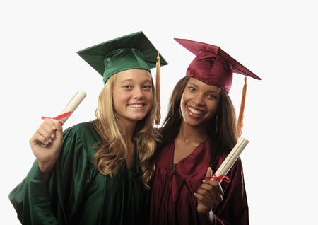 two female graduates in cap and gown with diplomas photo