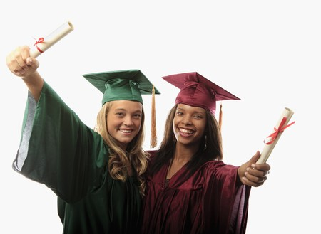 two female graduates in cap and gown with diplomas Stock Photo