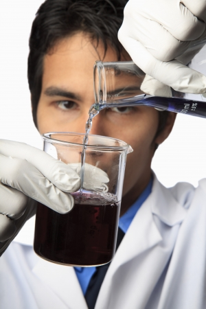 lab technician with beaker and flask, pouring Stock Photo