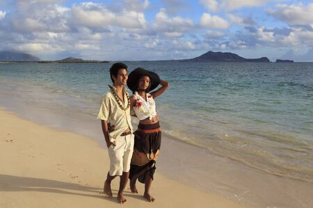 young mixed couple walk on a tropical beach together photo