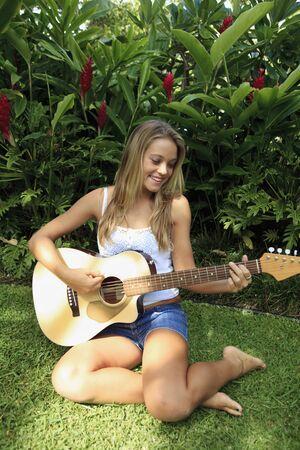 teenage girl playing guitar in her backyard Stock Photo - 7479426