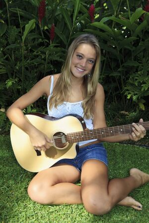 teenage girl playing guitar in her backyard Stock Photo - 7479425