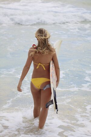 girl in a yellow bikini with her surfboard photo