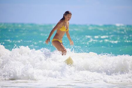 teenage girl in bikini surfing in Hawaii