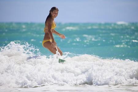 teenage girl in bikini surfing in Hawaii photo
