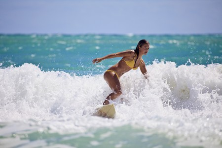 surfing beach: teenage girl in bikini surfing in Hawaii