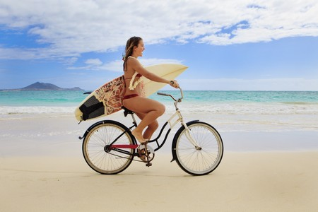 teenage girl with surfboard and bicycle on kailua beach photo