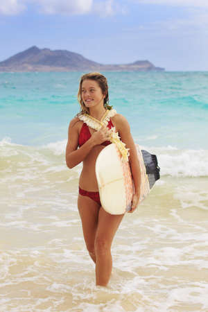 teenage girl in the ocean with her surfboard  photo