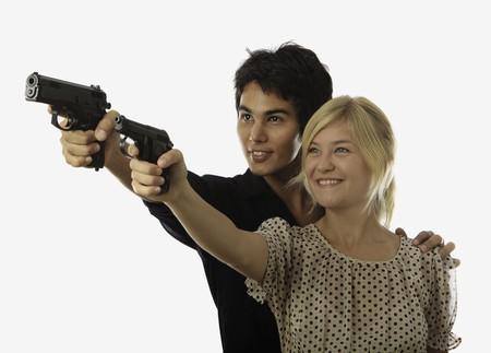 mujer con pistola: hombre ense�a a una joven mujer acerca de un tiroteo
