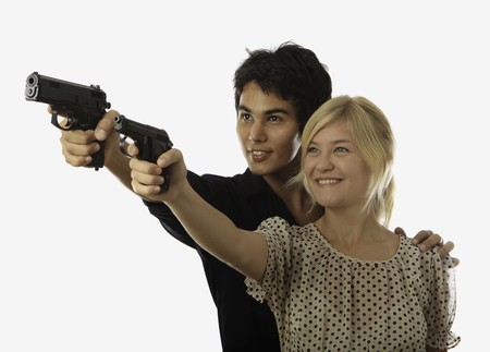teaches: man teaches a young woman about shooting