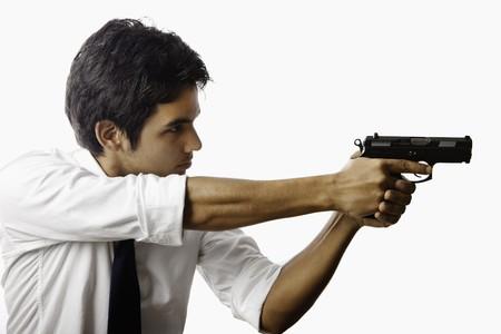 사격: young asian man with automatic pistol 스톡 사진