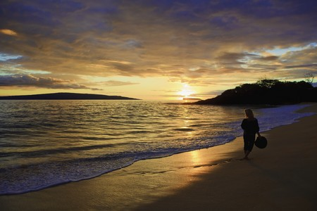 woman in her fifties walking on a maui beach photo