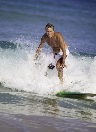 sixty-four year old man surfing in hawaii photo