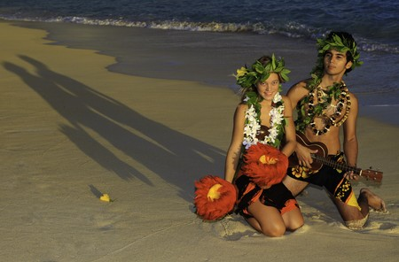 couple dancing hula on the beach at sunrise photo