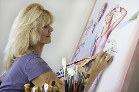 artist in her fifties painting on canvas photo
