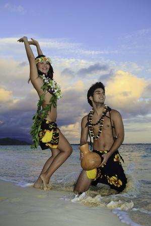 Pareja bailando el hula por el océano en hawaii Foto de archivo