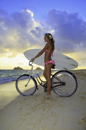 pink bike: girl in pink bikini with bike and surfboard