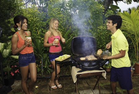 three friends at a barbecue party in hawaii