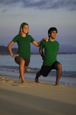 couple doing yoga, stretches on the beach photo