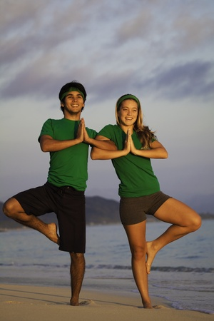couple doing yoga, stretches on the beach Stock Photo - 8828329