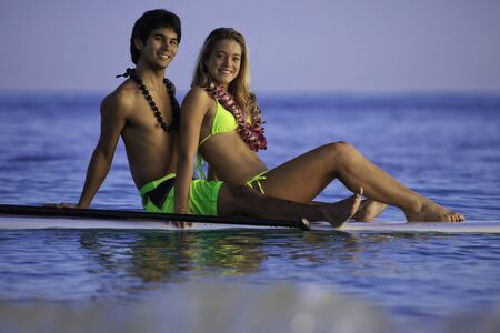 young couple on a paddleboard in hawaii photo