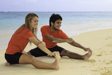 young couple exercising on the beach photo