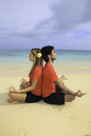 young couple meditating on the beach photo