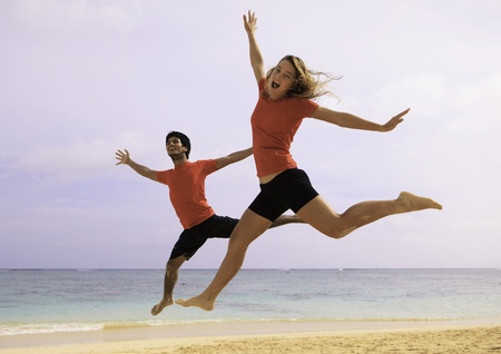 young couple jumping in the air at a beach photo