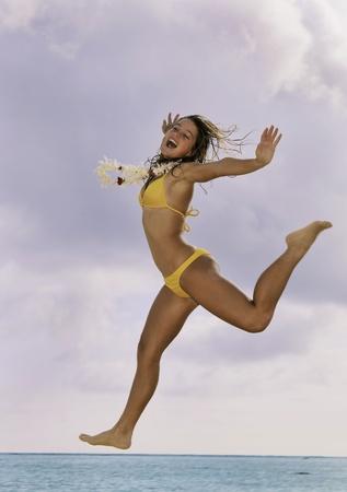 pretty girl in bikini with lei jumping in air Stock Photo