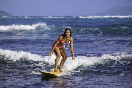 teen girl bikini: teenage girl in pink bikini surfing in hawaii Stock Photo