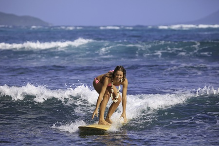 teenage girl in pink bikini surfing in hawaii photo