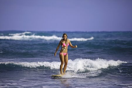 teenage girl in pink bikini surfing in hawaii 免版税图像