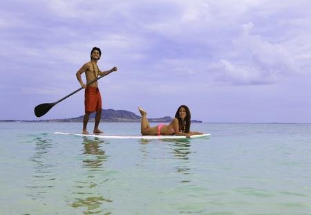 beachboy with girl in bikini on paddle board  photo