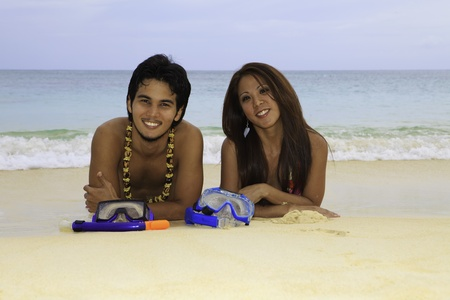 asian couple lounging on a sandy beac photo