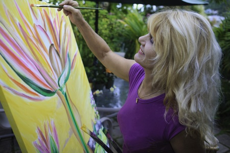 female artist in her fifties painting on canvas